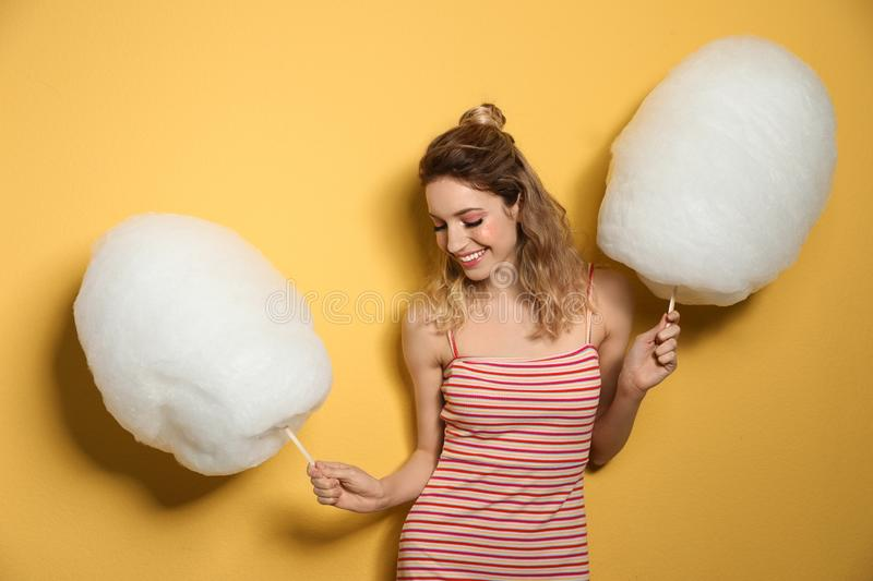 Portrait of pretty young woman with cotton candy on background royalty free stock photos