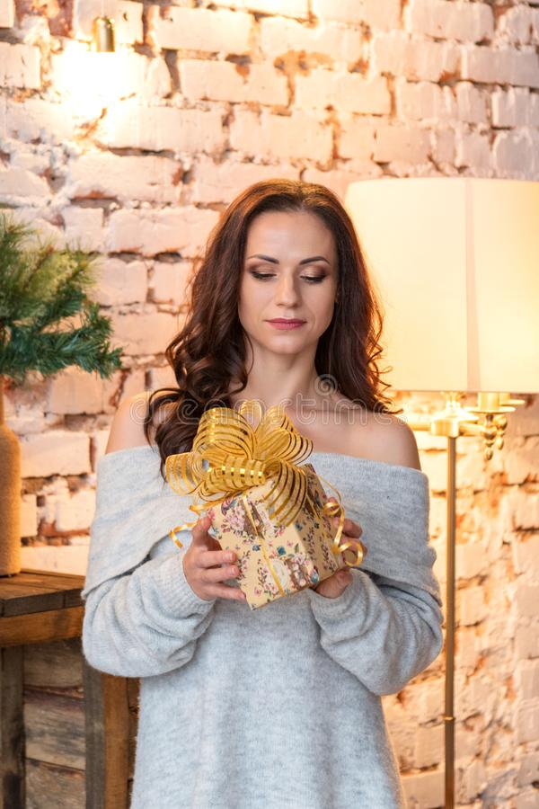 Portrait of a pretty young woman in a cozy sweater examines a gift in a festive package royalty free stock photos