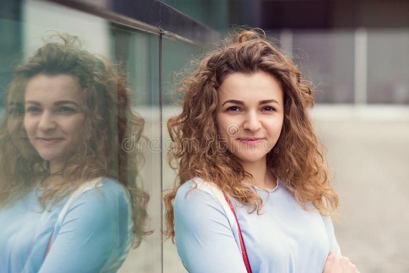 Portrait of pretty young woman with curly hair. In the city royalty free stock photo