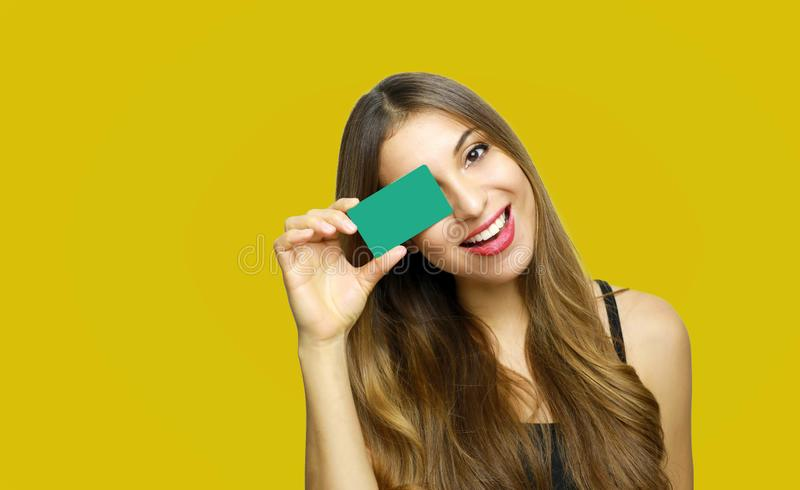 Portrait of a pretty young woman holding credit card at her face isolated over yellow background stock photo