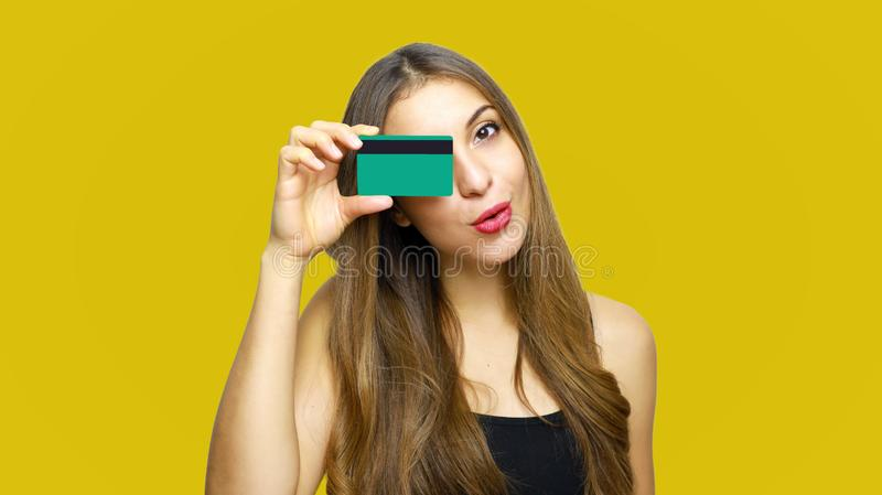 Portrait of a pretty young woman holding credit card at her face isolated over yellow background royalty free stock image
