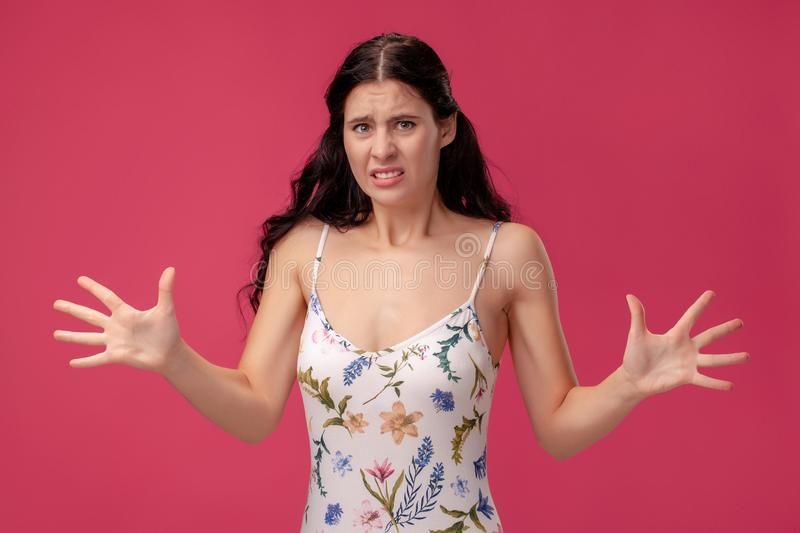 Portrait of a pretty young woman in a light dress standing on pink background in studio. People sincere emotions. stock photography