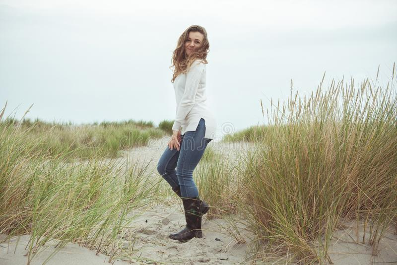 Portrait of pretty young woman posing on the Baltic sea beach in autumn stock photography