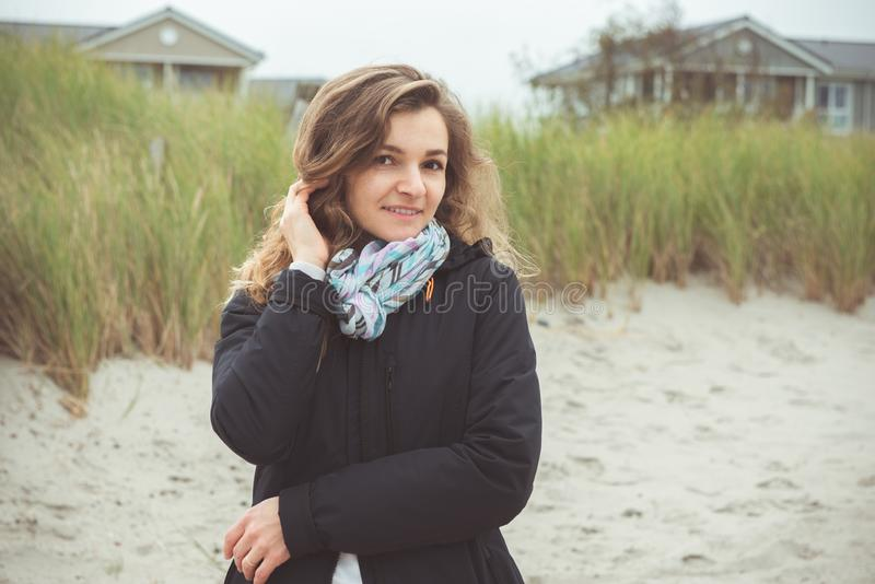 Portrait of pretty young woman posing on the Baltic sea beach in autumn royalty free stock image