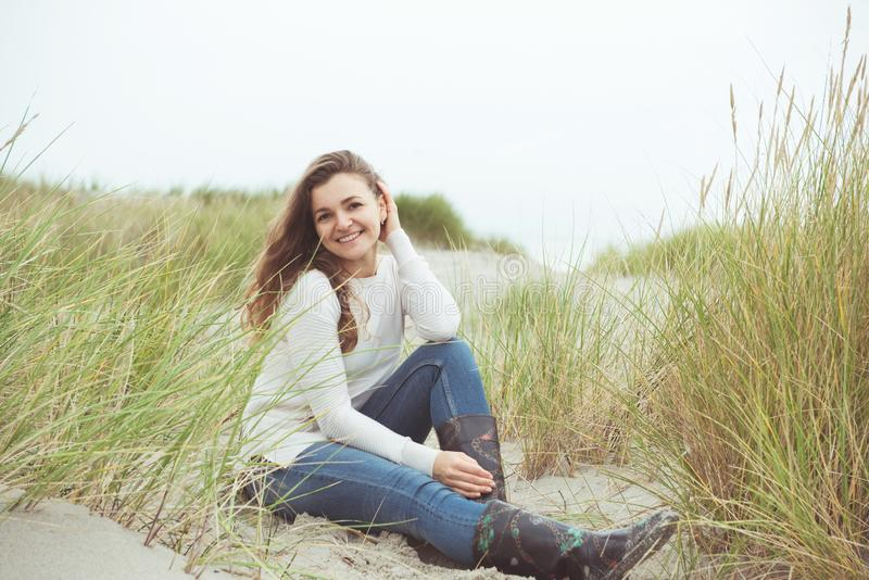 Portrait of pretty young woman posing on the Baltic sea beach in autumn royalty free stock photo