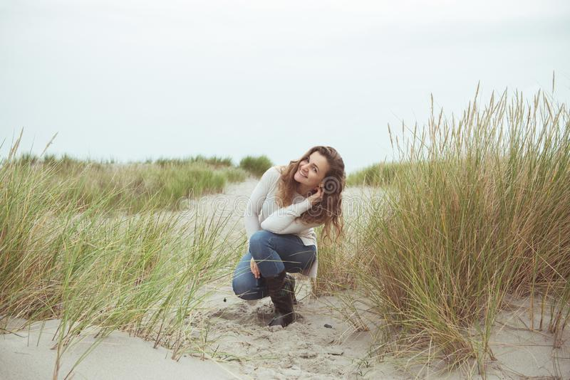 Portrait of pretty young woman posing on the Baltic sea beach in autumn stock photo