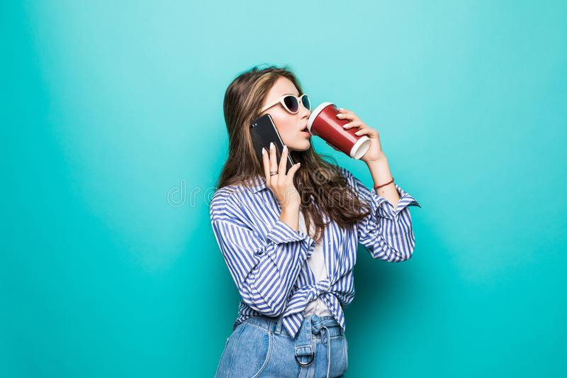 Portrait of a pretty young woman in sweater using mobile phone while holding takeaway coffee cup isolated over blue background stock photo