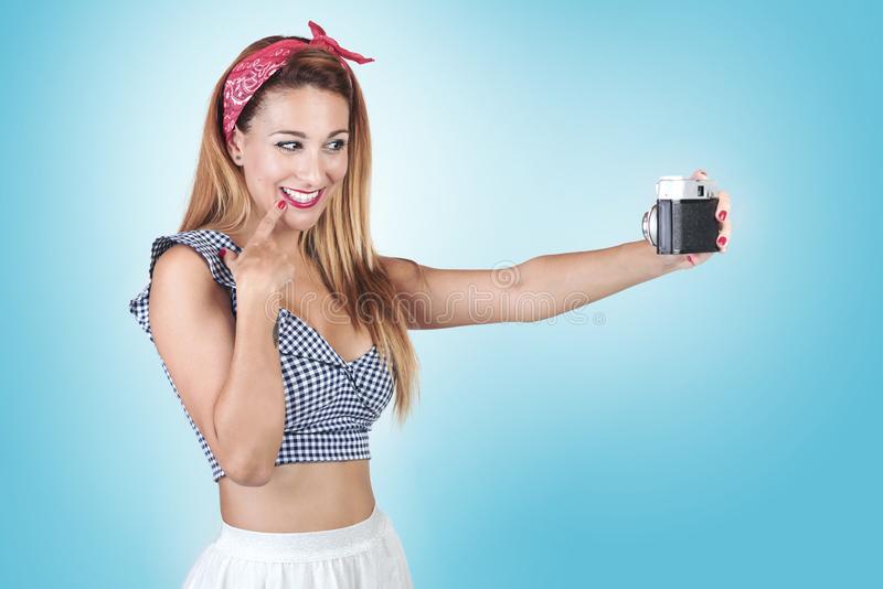 Portrait of pretty young woman using a camera. On blue background stock image