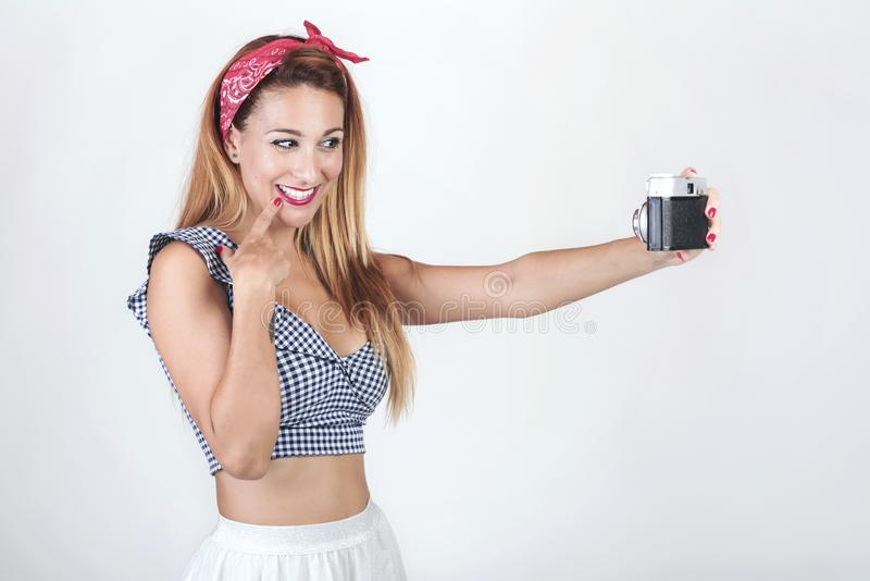 Portrait of pretty young woman using a camera. On White background stock images