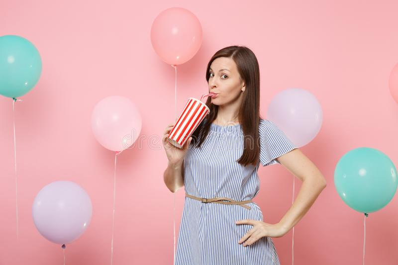 Portrait of pretty young woman wearing blue dress drinking cola or soda from plastic cup on pastel pink background with. Colorful air balloons. Birthday holiday stock images