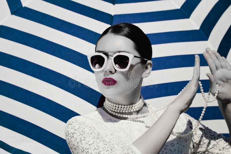 Portrait of a pretty young woman in white lace dress, white pearl necklace and light pink sunglasses. With bright painted lips next to a striped background stock photography
