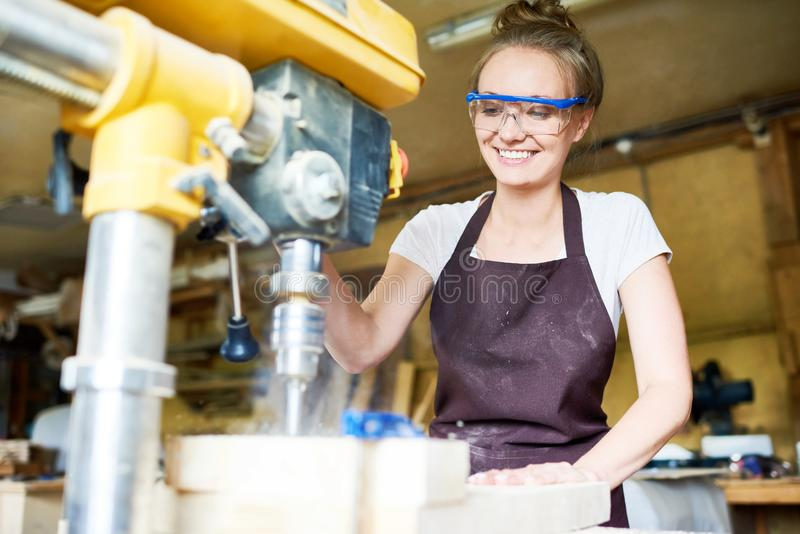 Portrait of Pretty Young Woodworker. Attractive young woodworker with toothy smile using drill press machine in order to make holes in wooden plank, blurred stock photo