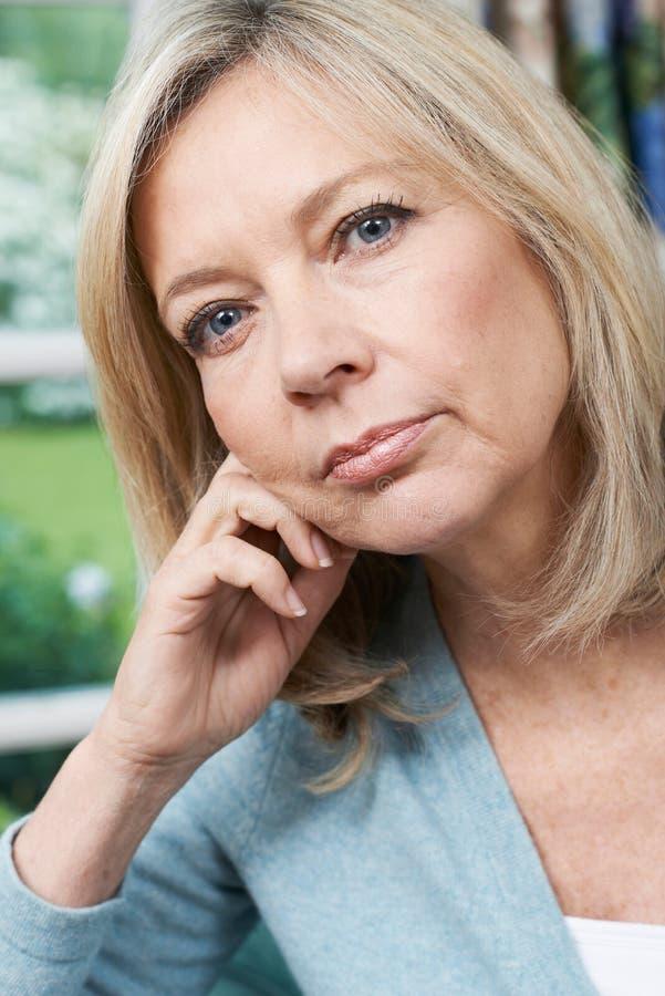 Portrait principal et d'épaules de femme mûre réfléchie à la maison photos stock