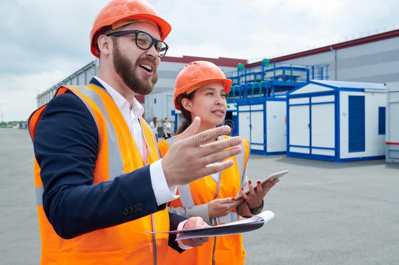 Factory Workers Outdoors. Portrait of production foreman wearing hardhat and holding clipboard talking to female factory employee outdoors while pointing royalty free stock images