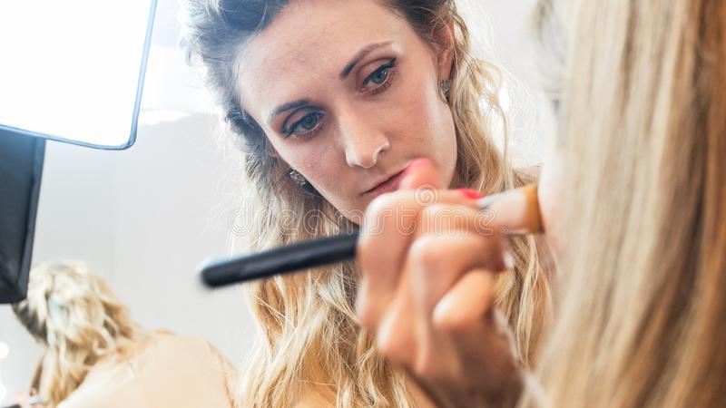 Closeup portrait of profesional makeup artist working in beauty studio royalty free stock photography