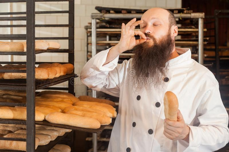 Portrait of professional adult male chef with long beard in white uniform standing in his workplace and cook with taste approval royalty free stock photo