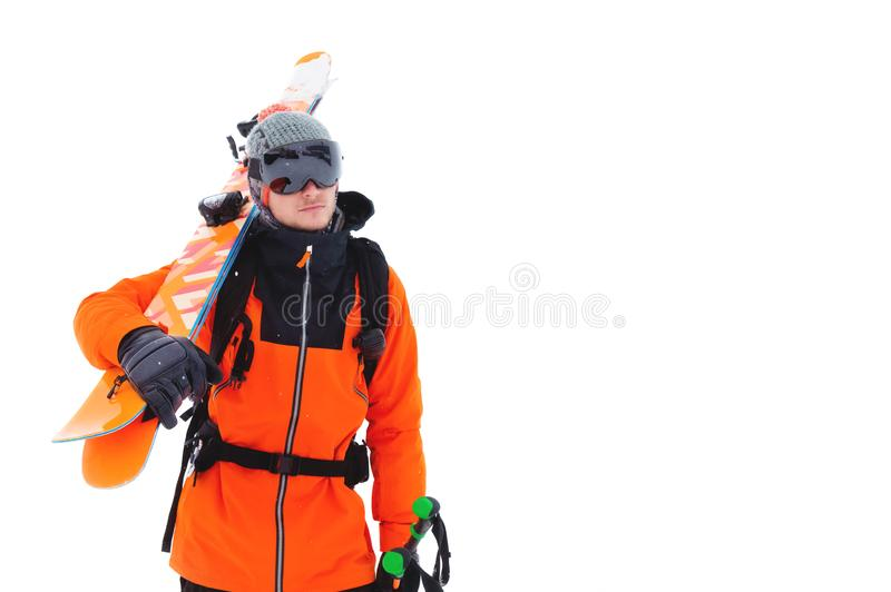 Portrait of a professional athlete skier in an orange jacket wearing a black mask and with skis on his shoulder looks stock photography