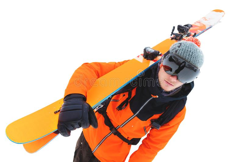 Portrait of a professional athlete skier in an orange jacket wearing a black mask and with skis on his shoulder looks stock image