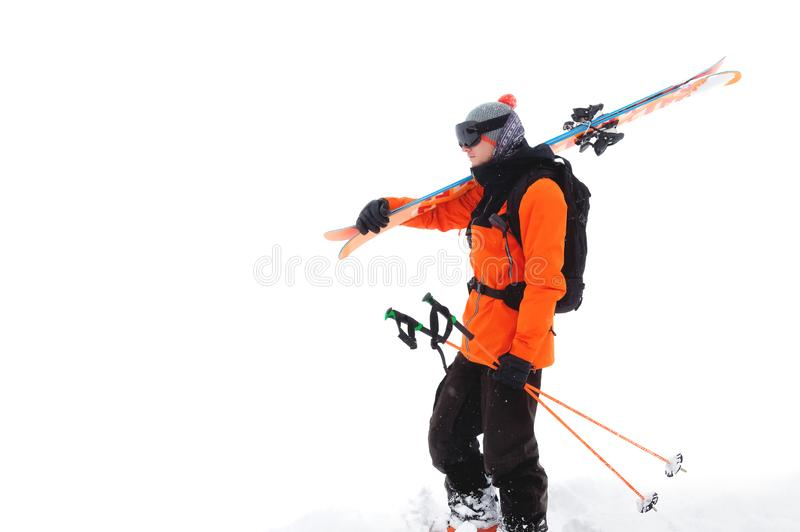 Portrait of a professional athlete skier in an orange jacket wearing a black mask and with skis on his shoulder looks royalty free stock photography