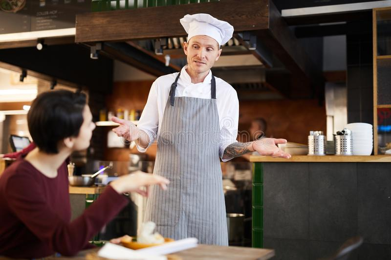 Client Complaining in Restaurant. Portrait of professional chef apologizing to client in restaurant, copy space stock image
