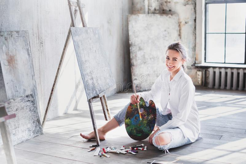 Portrait professional female artist painting on canvas in studio. Woman painter painting at workspace royalty free stock photos