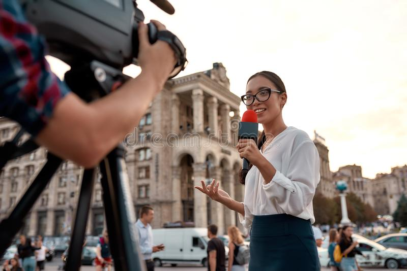 More news. More often. TV reporter presenting the news outdoors. Journalism industry, live streaming concept stock photos