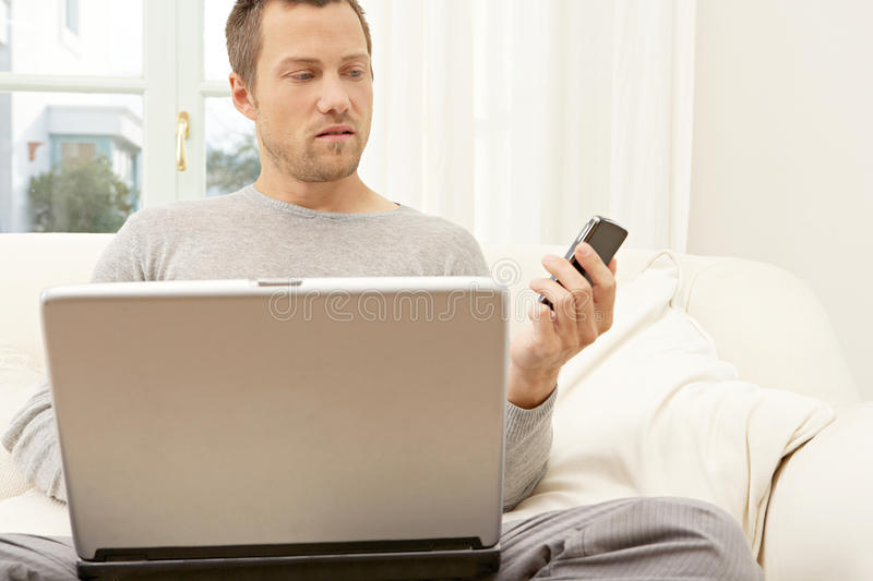 Download Portrait Of Professional Man With Laptop And Smart Phone At Home. Stock Photo - Image: 29315030