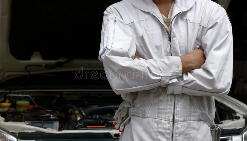 Portrait of professional mechanic in uniform crossing one`s arms with hood at repair garage. Car insurance concept. Portrait of professional mechanic in uniform royalty free stock images