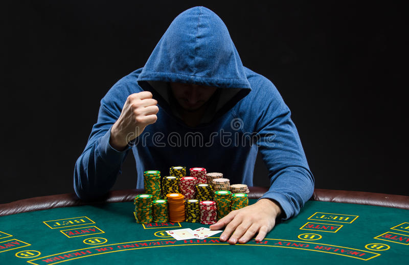 Portrait of a professional poker player sitting at pokers table. Portrait of a professional poker player sitting at a poker table with poker chips on black stock photography