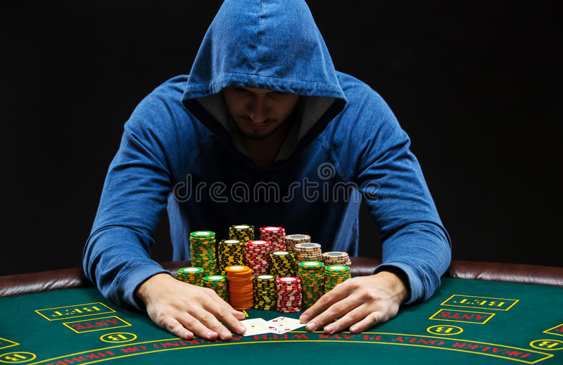 Portrait of a professional poker player sitting at pokers table. Portrait of a professional poker player sitting at a poker table with poker chips trying to hide royalty free stock photos