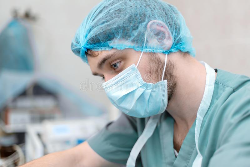 Portrait of professional surgeon focused on working process stock image