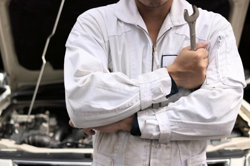 Portrait of professional young mechanic man in uniform holding wrench against car in open hood at the repair garage. Portrait of professional young mechanic man stock image