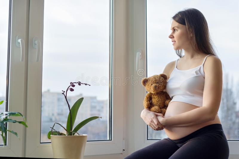 Portrait in profile of beautiful young pregnant woman brunette sitting near panoramic window with toy teddy bear. Dreaming female looking out the window royalty free stock photography