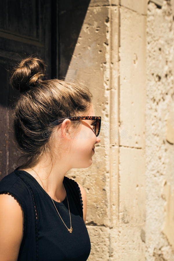 Portrait in profile of a pretty teenage girl with sunglasses royalty free stock image