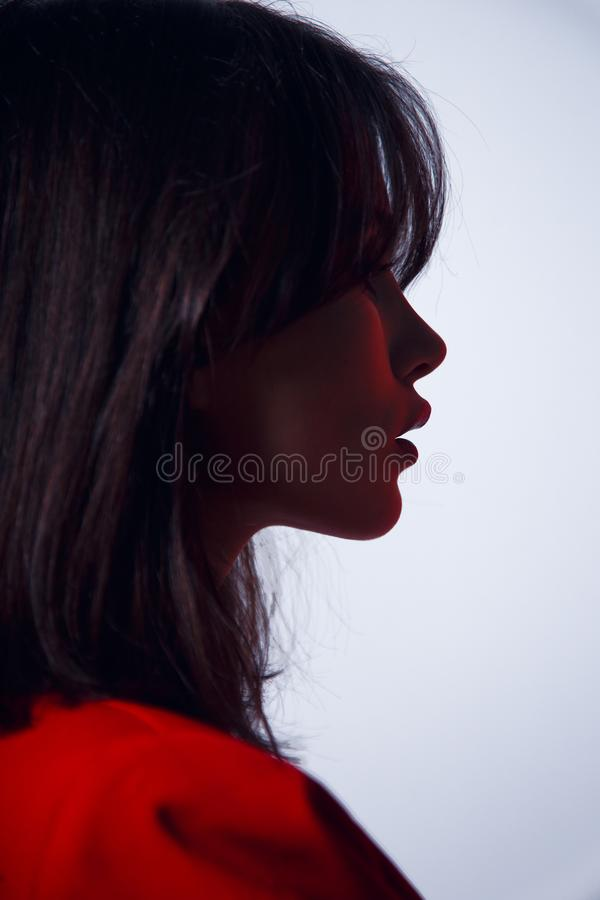 Portrait in profile a sexy brunette model, with big lips in red suit, elegant hairstyle, isolated on a white background. royalty free stock photo