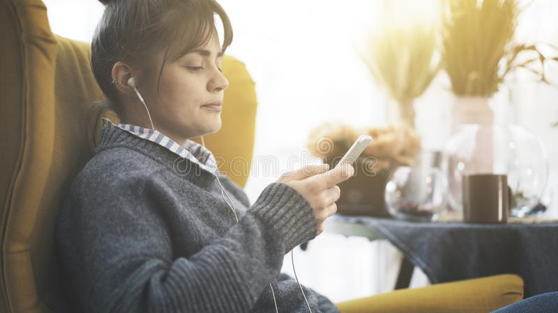 A portrait profile of a girl in earphones holding a phone royalty free stock image