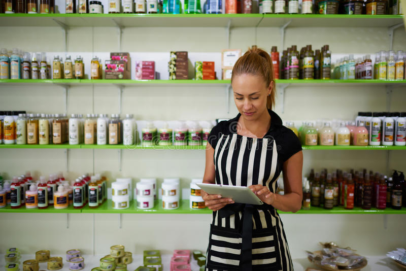 Portrait of a prosperous woman entrepreneur using touch pad for check the number of cosmetic products, royalty free stock photography