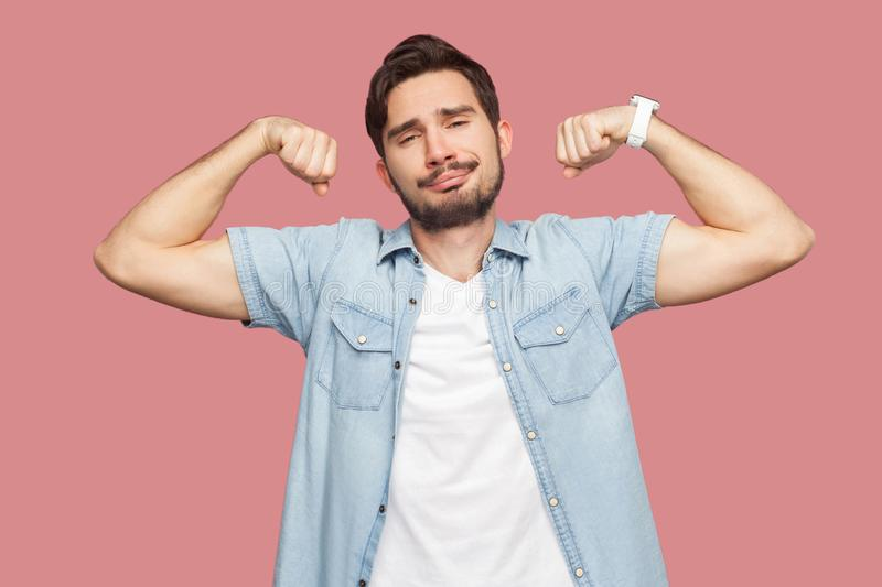 Portrait of proud satisfied handsome bearded young man in blue casual style shirt standing in body building pose and showing his royalty free stock image