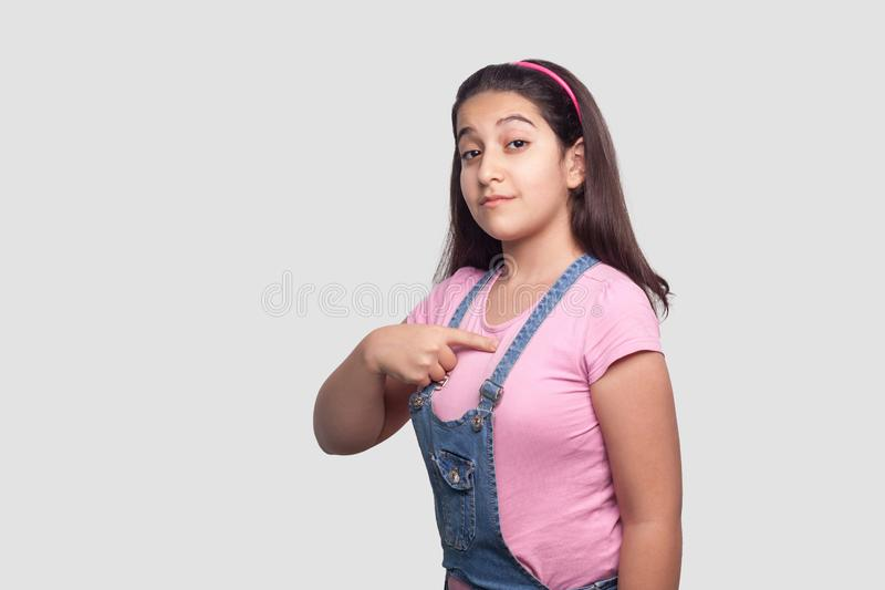Portrait of proud serious beautiful brunette girl in casual pink t-shirt and blue overalls standing, pointing herself and looking. With satisfied face. studio stock images