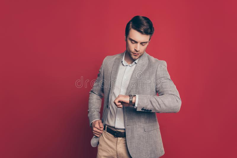 Portrait of punctual, virile, harsh, stunning financier looking. At his watch on arm, nervous that his partner is late, on red background, checking time stock photo