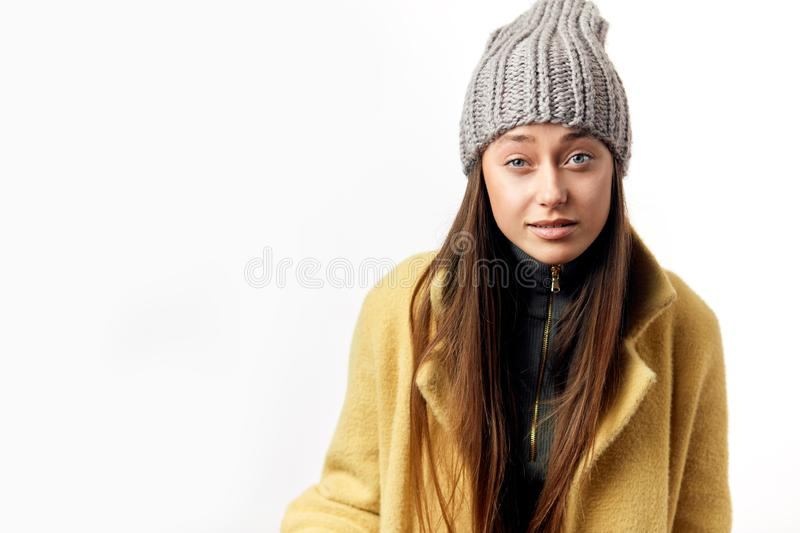 Indignant puzzled young female hipster in winter topcoat and trendy hat royalty free stock images
