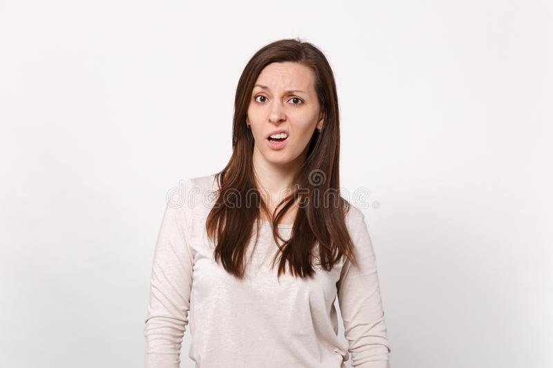 Portrait of puzzled concerned dissatisfied young woman in light clothes looking camera isolated on white wall background stock photography