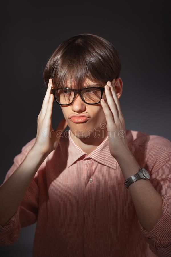 Portrait of puzzled funny young Caucasian man wearing glasses, shirt in a strip siting indoors with happy face and royalty free stock photography