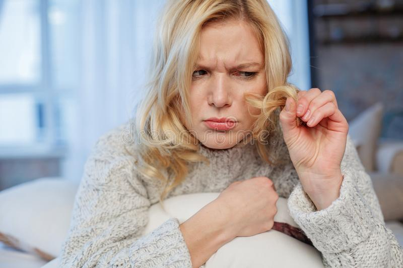 Confused woman observing own topknot. Portrait of puzzled girl sitting at home. She is holding lock of hair and looking at it with sadness stock images