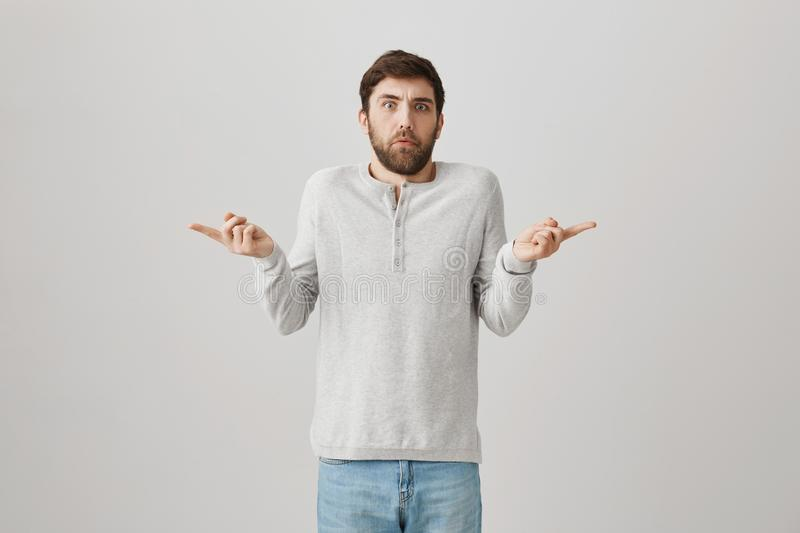 Portrait of puzzled good-looking man pointing at both sides and expressing confusion about which side he should go or. Choose, standing against gray background royalty free stock photo