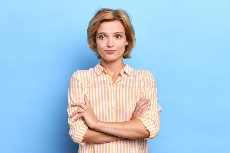 Portrait of a puzzled surprised scared woman standing with arms folded royalty free stock images