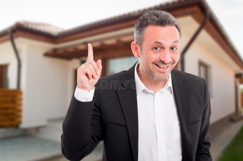 Portrait of real estate agent pointing finger up stock image