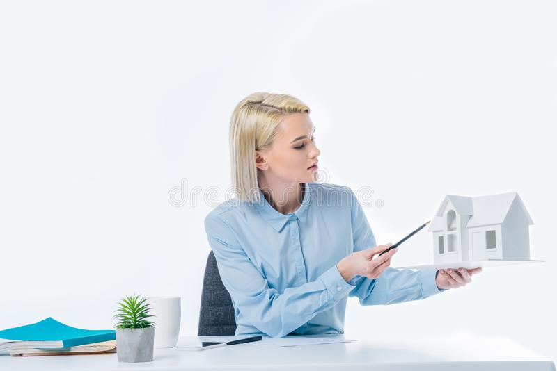 portrait of real estate agent pointing at house model in hand stock image