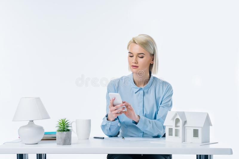 portrait of real estate agent using smartphone at workplace royalty free stock photography