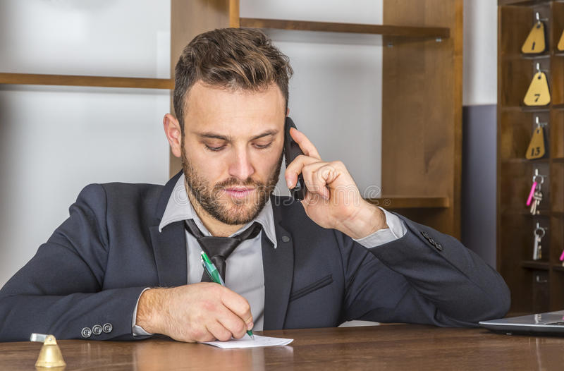 Portrait of a Receptionist. Taking notice on a piece of paper while he is on the phone at his desk in a small hostel royalty free stock image